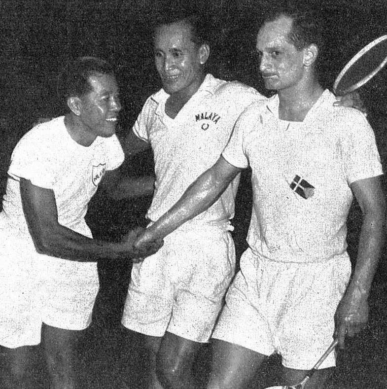 Ong poh lim (centre) watches as team mate wong peng soon and ole jensen (den) shake hands after their 1955 thomas cup match - badminton gazette oct 1955